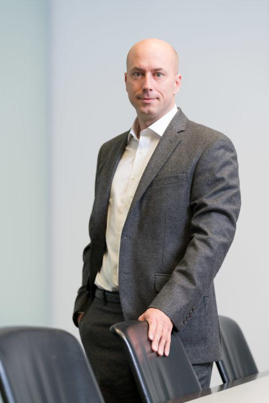 Businessportrait: Hochformatfoto eines Managers. Ein großer Konferenzraum ist ein geeigneter Ort für viele unterschiedliche Portraits in kurzer Zeit.