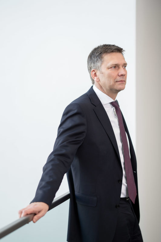Portrait of a managing director: A male executive loosely leaning on a modern glass railing. He wears a tie and looks relaxed into the room.