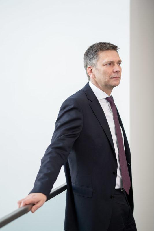 Geschäftsführerportrait: Eine männliche Führungskraft stützt sich locker auf eine moderne Glasreling. Er trägt Krawatte und schaut entspannt in den Raum.