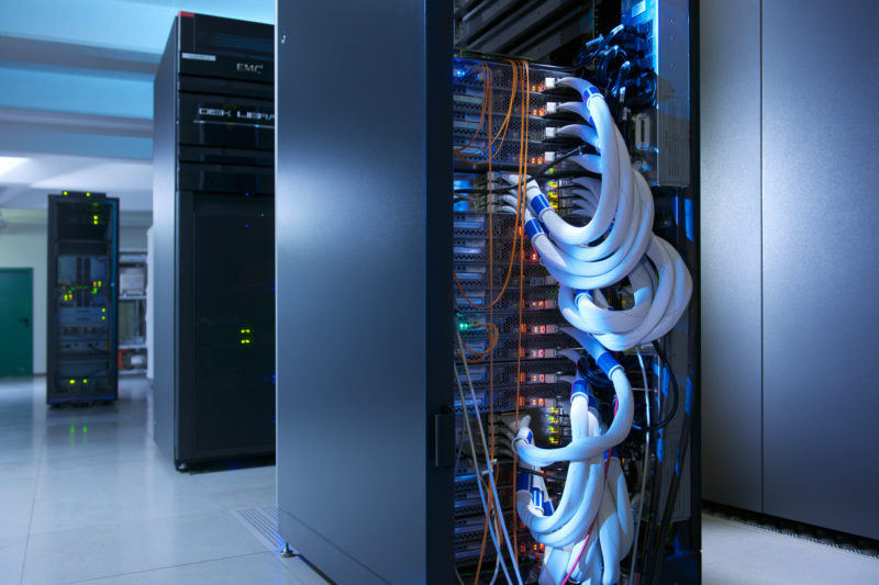 Industrial photography: In a cloud computing center the servers are located in rows in the dark.