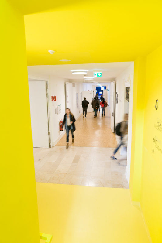 Architectural photography: View into the corridor of a private college, for which an abandoned monastery was rebuilt. A yellow staircase shows pupils changing classrooms during the break.
