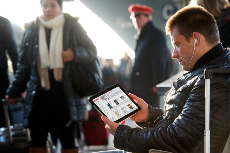 Reportage-Fotografie: Ein Mann sitzt am Bahnsteig und schaut auf sein Tablet-Computer. Im Ohr hat er Kopfhörer. Im Hintergrund steht ein Bahnmitarbeiter.