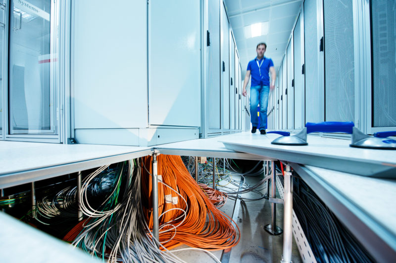 Industrial photography: View into the open double floor of a server room. You can see an incredible amount of data cables and power lines as an employee walks over the still-closed plates of the double floor between the server racks.