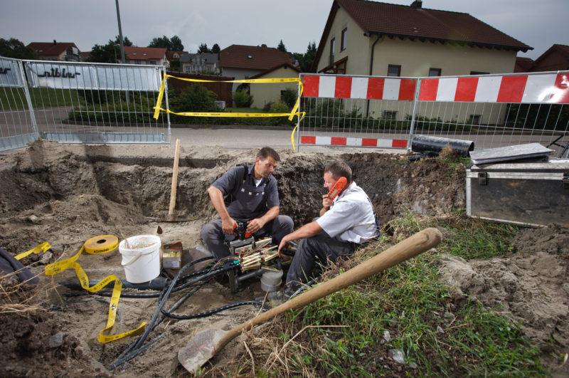 Industriefotografie: Zwei Techniker sitzen in einer Baugrube und arbeiten an Telefon- und Datenverbindungen für die Wohnsiedlung im Hintergrund.