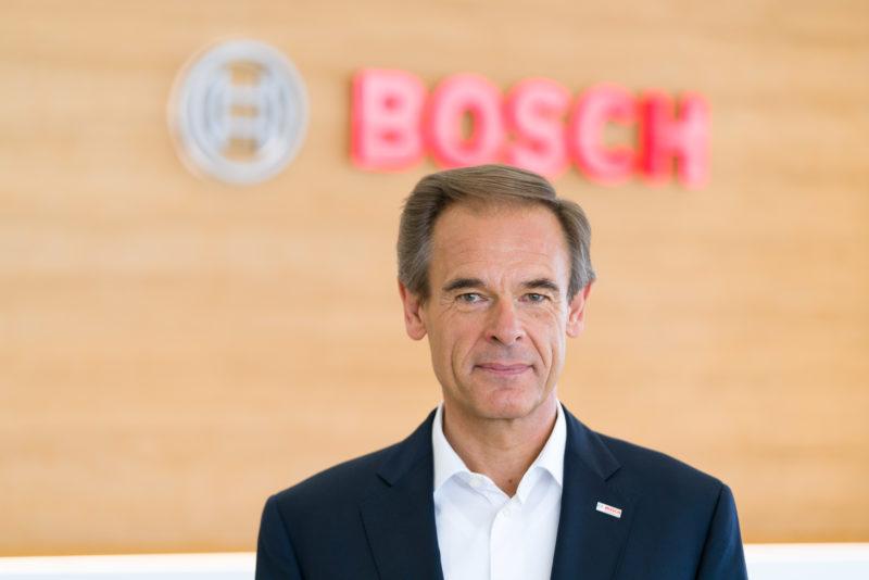Managerportrait: Dr. Volkmar Denner, Vorsitzender der Geschäftsführung der Robert Bosch GmbH vor dem Bosch Logo.