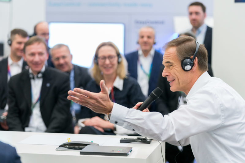 Editorial photography as event photography and fair photography: Volkmar Denner, Chairman of the Board of Management of Robert Bosch GmbH, at an event. During a technical discussion, he wears headphones from Bosch.