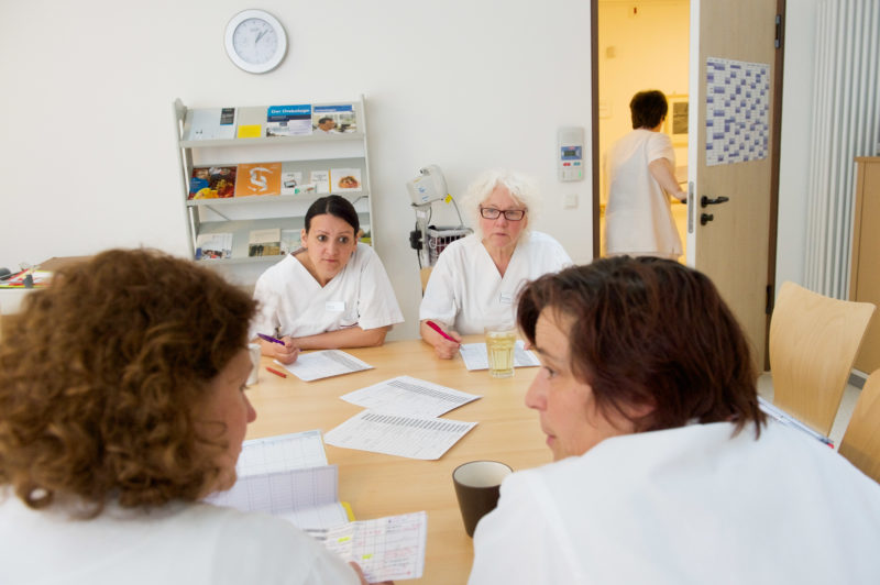 Healthcare photography: Nurses at a meeting in the duty room of a ward in a district hospital. A nurse leaves the room to respond to a patient call.