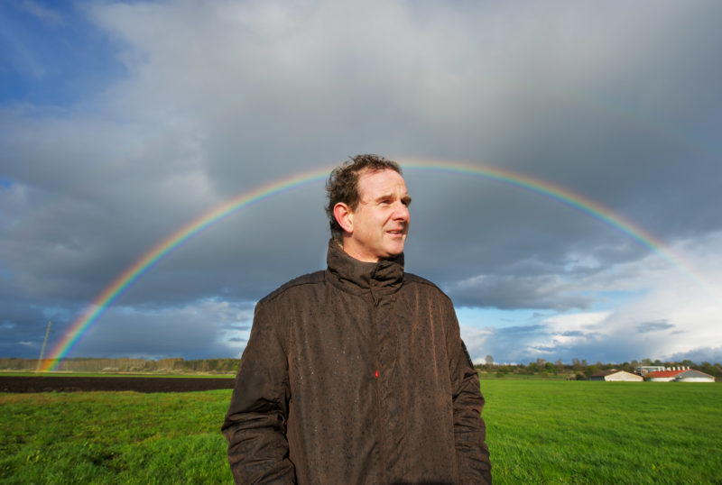 Employees photography: The archaeologist Dirk Krauße is standing on a field. It rains and before the dark clouds in the sky shines a rainbow.