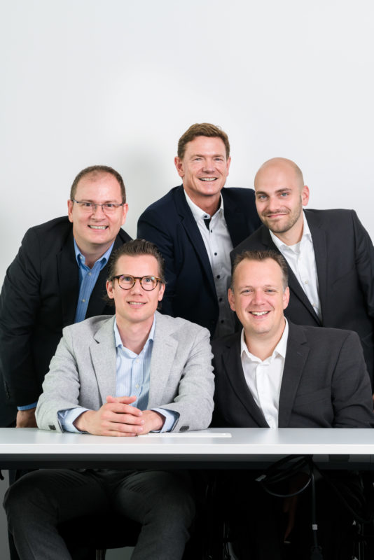 Group photo: Five participants of a discussion table laugh into the camera. They stand as close together as possible for the cover photo of a magazine.