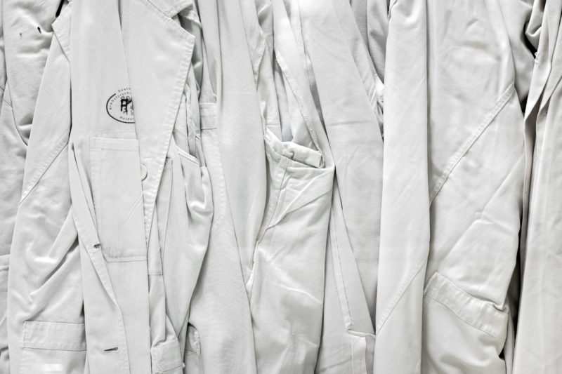 Science photography: Scientific photography:  White researchers coats hanging at a glass partition in the in the clean room laboratory at German Cancer Research Center in Heidelberg.