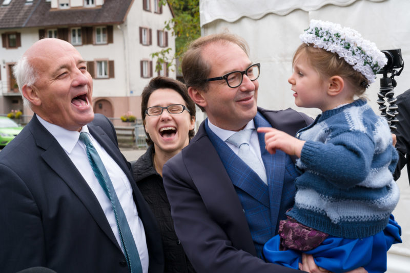 Editorial photography as event photography and fair photography: CSU politician Alexander Dobrindt visits an event in a small Bavarian town. A little girl in traditional costume is sitting on his arm.