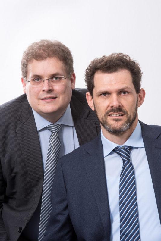 Managerportrait: Zwei Partner einer Firma im nahen Doppelportrait. Beide tragen blau gestreifte Krawatten. Der Hintergrund ist weiß.