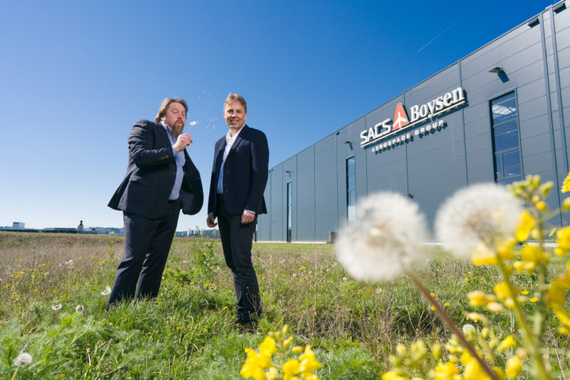 Managerportrait: Double portrait of two managers. They stand on a wild meadow in front of their modern company building, on which the logo of the company is attached. One has mature dandelion stems in his hand and blows the dandelion flowers to his colleague.