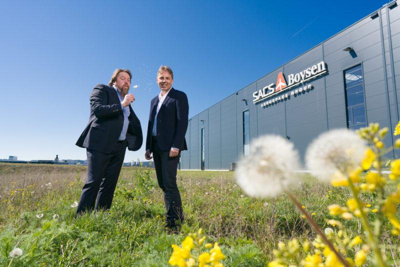 Managerportrait: Doppelportrait von zwei Managern. Sie stehen auf der wilden Wiese vor ihrem modernen Firmengebäude, auf dem das Logo der Firma angebracht ist. Der eine hat reife Löwenzahnstengel in der Hand und bläst die Pusteblumen zu seinem Kollegen.