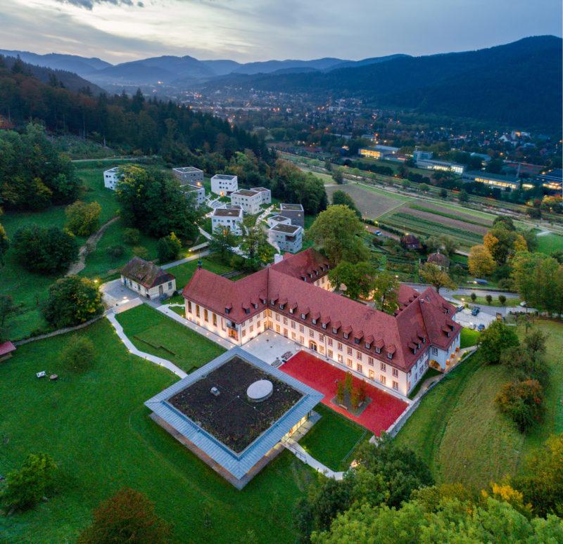 Luftaufnahmen und Drohnenfotografie: In Panoramatechnik fotografierte Drohnenaufnahme einer beleuchteten internationalen Schule bei einbrechender Nacht.