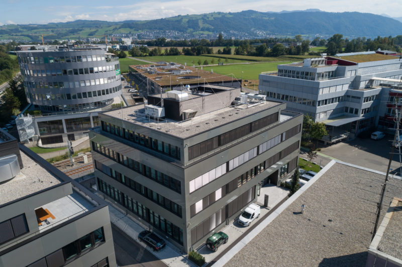 Aerial and Drone photography: A new office building in an industrial area. One sees the beautiful surrounding mountain landscape.