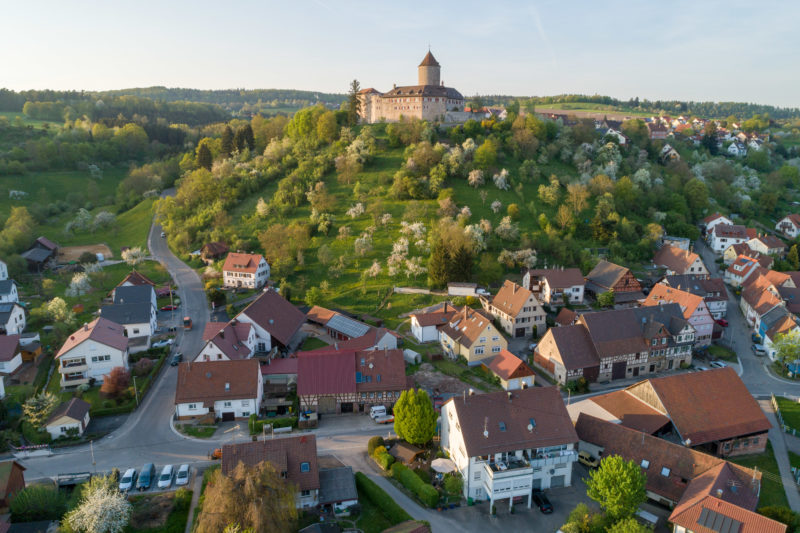Landscape photogaphy: Aerial and Drone photography: Reichenberg Castle near Oppenweiler in the evening sunlight. Blossoming fruit trees line the castle hill, at the foot of which the village is situated.