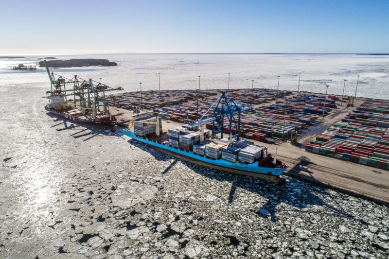 Luftaufnahmen und Drohnenfotografie: Ein finnischer Containerhafen der von Eisschollen fast vollständig eingeschlossen ist.