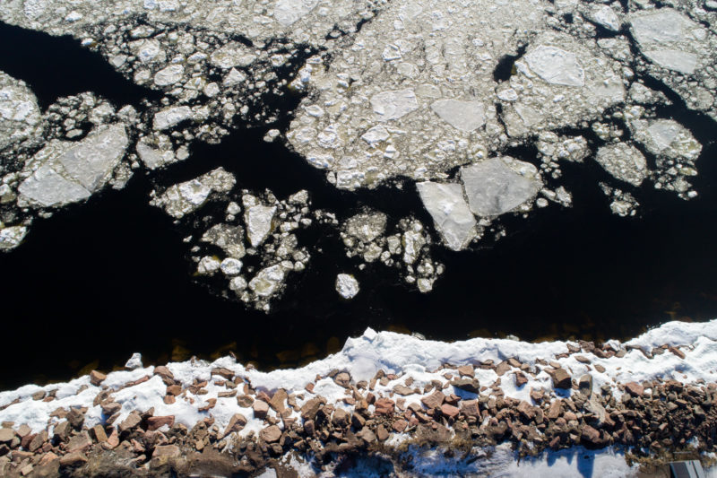 Luftaufnahmen und Drohnenfotografie: Senkrechte Drohnenaufnahme vom Eis auf dem Waser und dem Schnee am steil abfallenden steinigen Ufer an der finnischen Ostseeküste im Winter.