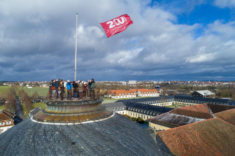Luftaufnahmen und Drohnenfotografie: Auf dem Dach des Schlosses an der Universität Hohenheim wird anlässlich des 200 jährigen Jubiläums eine Fahne gehisst. Am dunkelblauen Himmel sind dramatische Wolken.
