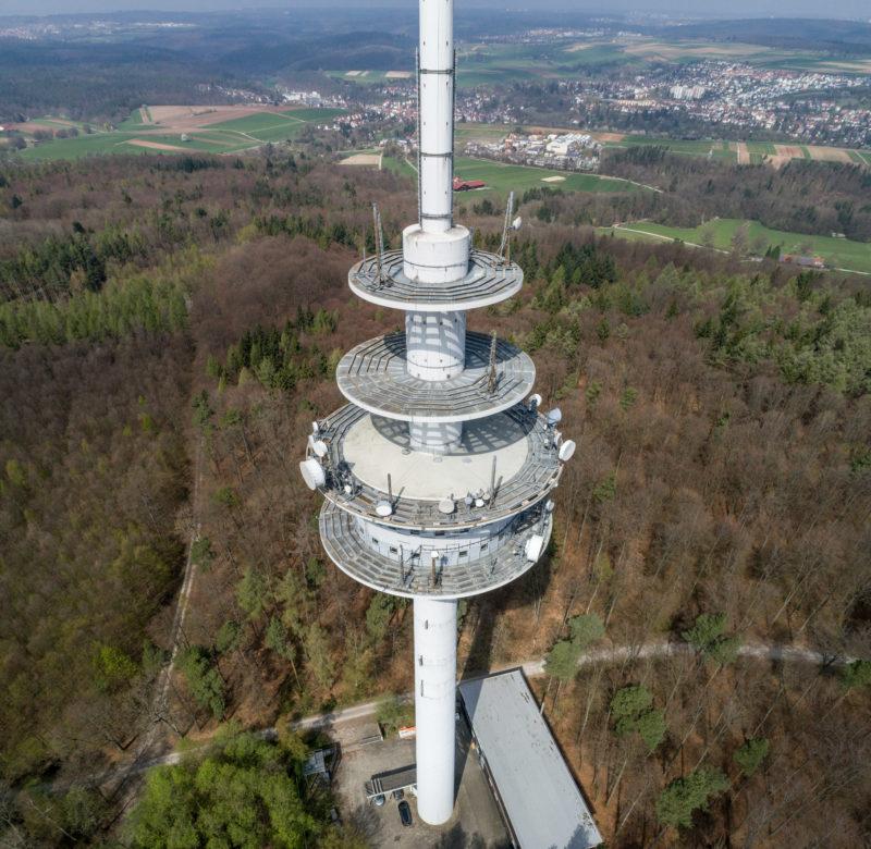 Luftaufnahmen und Drohnenfotografie: Ein Funkturm im Wald. Im Hintergrund sieht man den nächst gelegenen Ort mit Wiesen und Straßen.