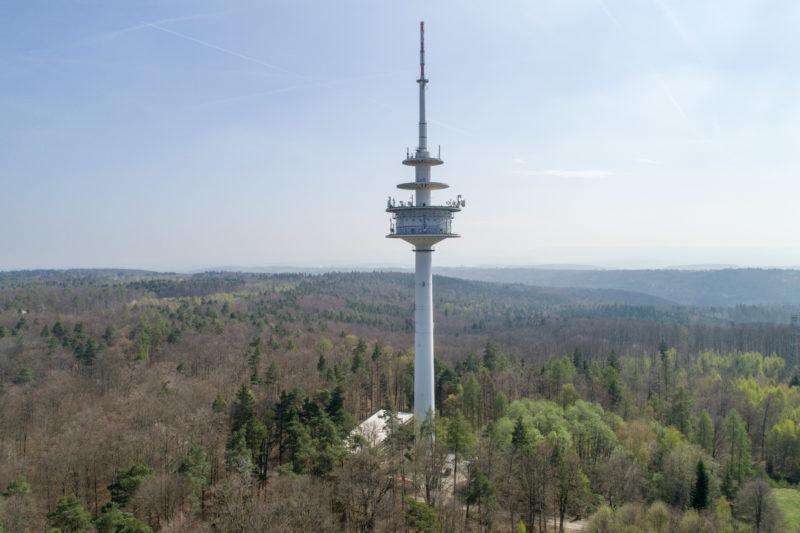 Luftaufnahmen und Drohnenfotografie: Ein Funkturm in der bewaldeten sanften Hügellandschaft der schwäbischen Alb.