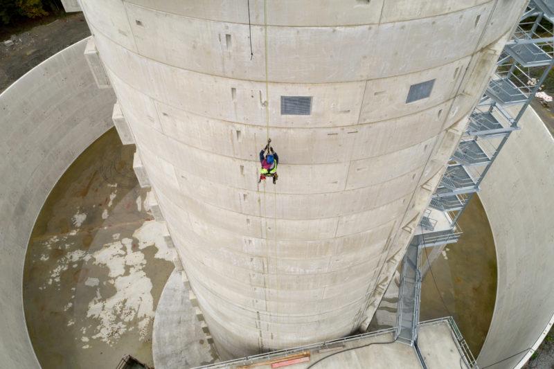 Luftaufnahmen und Drohnenfotografie: Ein Industriekletterer seilt sich von einem Windkraftwerksturm ab.
