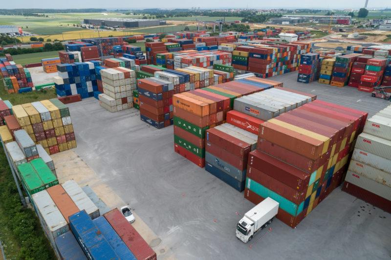 Luftaufnahmen und Drohnenfotografie: Ein weisser LKW in einem Test eines Positionierungssystemes innerhalb eines Containerlagers.
