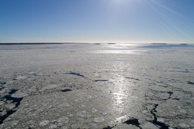 Luftaufnahmen und Drohnenfotografie: Die mit einer Drohne fotografierte Gegenlichtaufnahme zeigt die vereiste Ostsee vor Finnland bei bestem aber sehr kaltem Wetter.