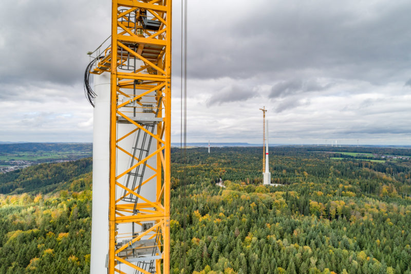 Aerial and Drone photography: At the top of the tower of a wind turbine, which is currently under construction, cables protrude which will later carry the electrical current from the nacelle downwards.