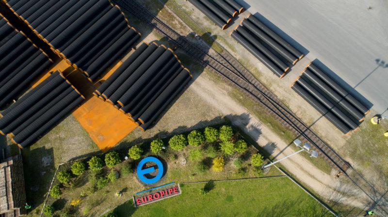 Luftaufnahmen und Drohnenfotografie: Blick senkrecht von oben auf gelagerte Pipeline-Großrohre aus Stahl.