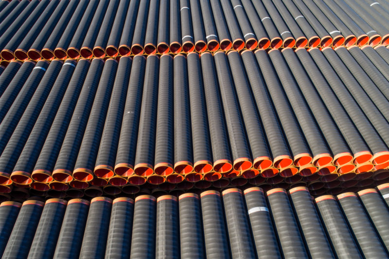 Aerial and Drone photography: Pipes for a pipeline under construction are stacked in a large outdoor storage facility.