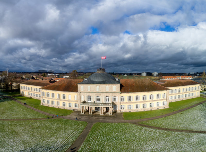 Luftaufnahmen und Drohnenfotografie: Das Schloss der Universität Hohenheim als Panoramaaufnahme. Auf der Kuppel des Hautgebäudes wird eine Fahne gehisst.