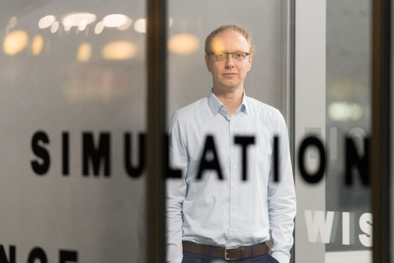 Editorial Photography: Scientist researches the interface between man and machine and the visual interaction required for this. The blurred writing at the entrance to the institute is a good foreground for another portrait photo of the scientist.