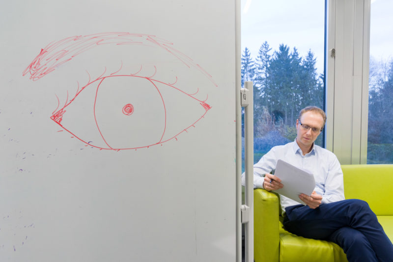 Editorial Photography: Scientist researches the interface between man and machine and the visual interaction required for this. Portrait with tablet on the sofa and a drawn eye on the wall.