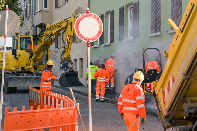 Reportage photography on a fiber optic construction site: The installation of fast Internet in an urban environment is very complex and requires a lot of manual work despite the use of machines.