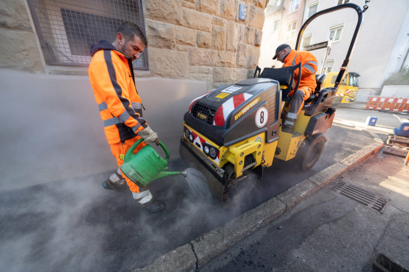 Reportage photography on a fiber optic construction site: To lay lines for fast Internet in an urban residential area, the sidewalk was opened and is now being tarred again.