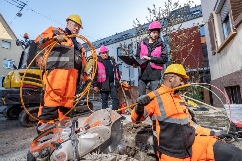 Reportage photography on a fiber optic construction site: The employees of the telecommunications company work closely with the workers of the construction company to ensure that the fiber optic lines for fast Internet are laid correctly.