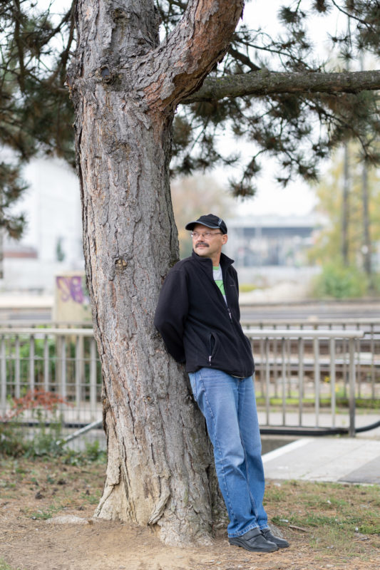 Editorial Portrait: For a staff magazine, a portrait was taken of an employee who, as a tree lover, supports an initiative that plants trees worldwide. Here he is leaning against an old tree in the city.