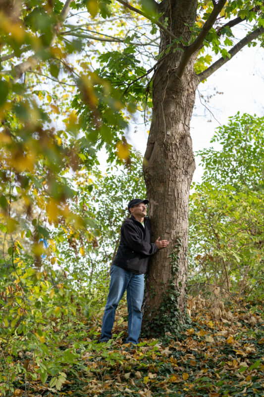 Editorial Portrait: A lover of trees clasps a tree in a city park. The portrait was photographed to support a tree-planting initiative for a staff magazine.