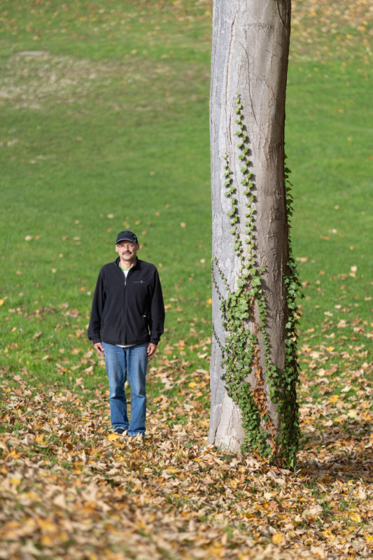 Editorial Portrait: A friend of trees stands next to the trunk of a park tree. Withered leaves surround him. Ivy is climbing up the trunk of the tree.