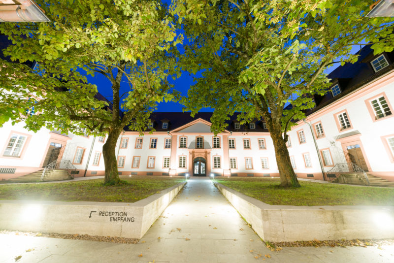 Architectural photography: The inner courtyard of a former monastery that is illuminated at night and now houses a private college. Trees and green areas line the way to the main entrance.