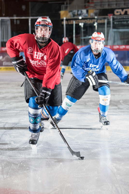 Employees photography: A young man playing ice hockey. In the background one of the pursuers of the opposing team.