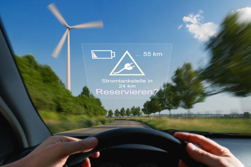 Fotomontage Elektromobilität: Ein Head-Up Display hilft bei Reservieren der nächsten Stromtankstelle. Im Hintergrund ein Windrad.