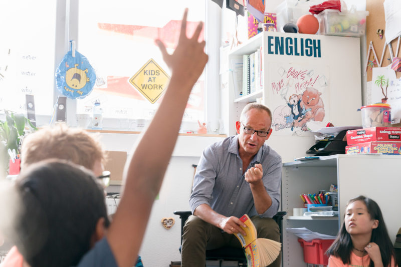 Editorial photography: A teacher at work: Editorial photography, subject learning and education: A teacher from an international school reads during English lessons a book and discusses with the children what he or she has heard.