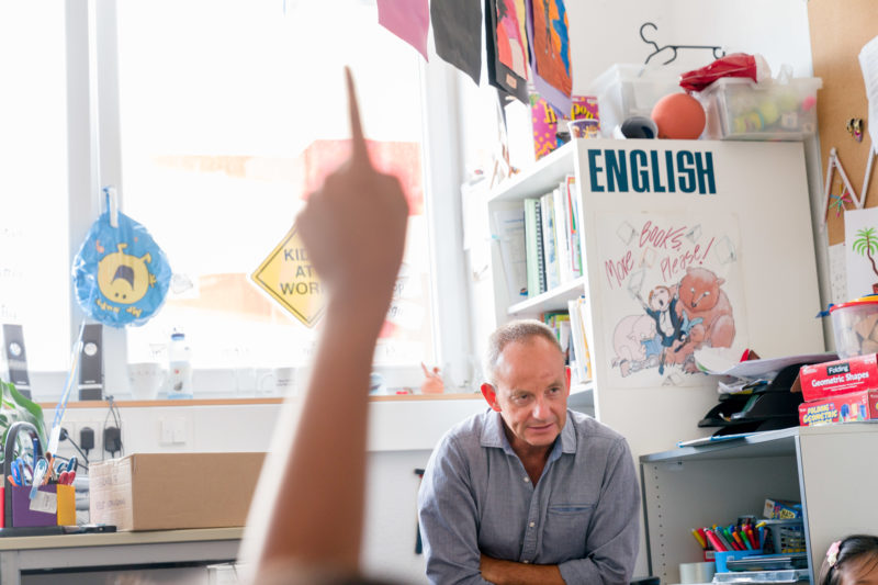 Editorial photography: An English teacher during class. He talks to the children and they give hand signals to answer his questions or to be allowed to say something.