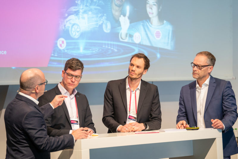 Event photography: A customer event of an IT company: In the case of a podium, the moderator can also be shown from behind, as long as all important people are well portrayed together.