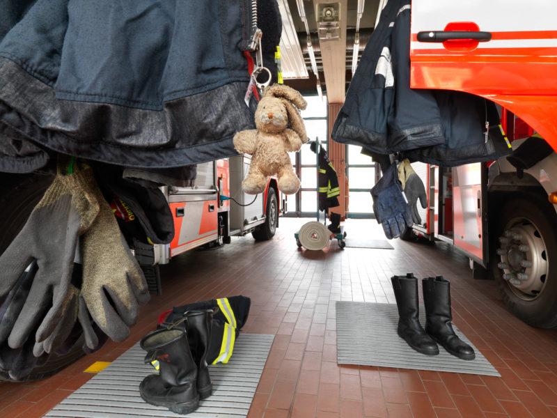 Reportagefotografie: In der Garage einer Feuerwache hängt die Einsatzkleidung an den geöffneten Fahrzeugtüren und die Stiefel stehen direkt davor. Am Reissverschluss einer Jacke hängt ein kleiner Stoffhase als Glücksbringer.