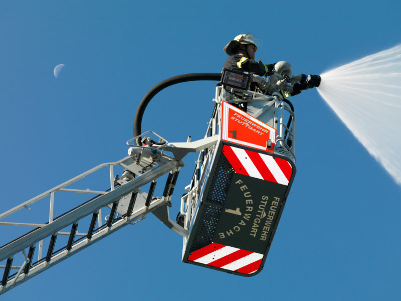 editorial photography: A fireman steers the open jet pipe in the basket of a turntable ladder. In the blue sky behind it is the crescent of the waning moon.