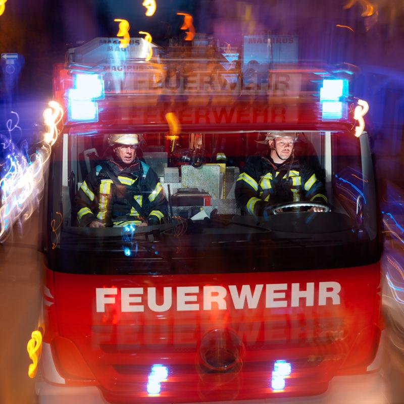 Luftaufnahmen und Drohnenfotografie: Reportagefotografie: Zwei Feuerwehrleute in ihrem Hilfeleistungslöschfahrzeug auf der nächtlichen Fahrt mit Blaulicht.
